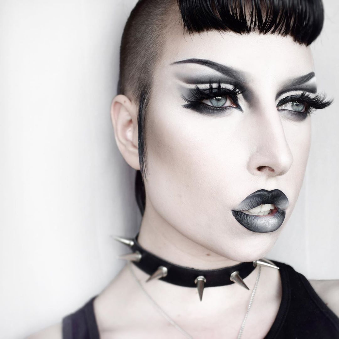 Stylish model wears a smokey eye makeup and a gradient lip look going from black to gray to white.