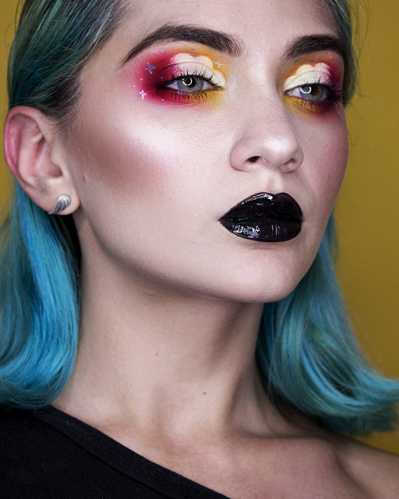 Model wears a shimmering eyeshadow with golden and red hues and a black lipstick.