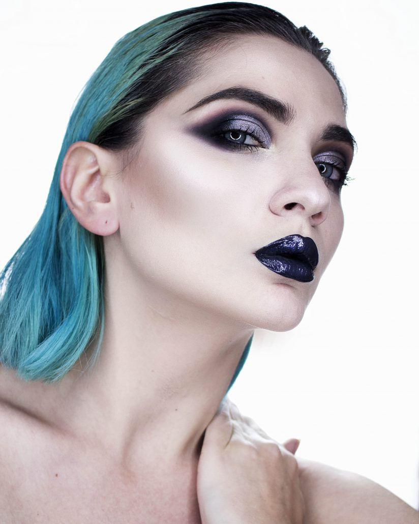 Model with teal hair is wearing dark, smokey eye makeup with black lipstick.