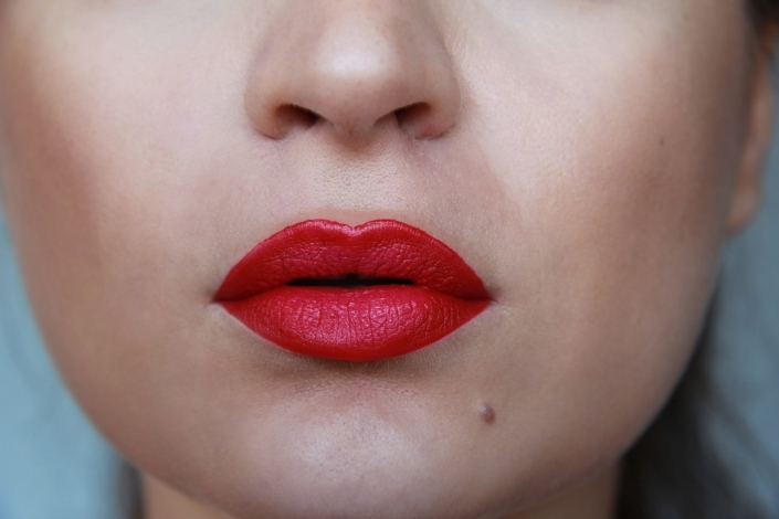 model pouts with a beautifully applied lipstick shade.