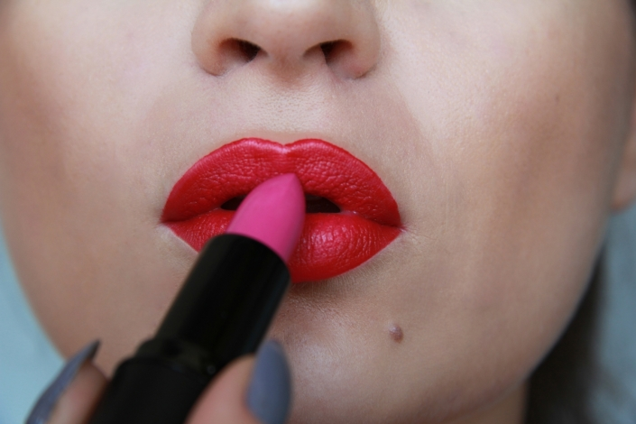 model uses lighter shade lipstick on the edges of her lips.